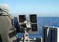 US Navy 040302-N-8955H-054 Signalman Joel Dollar, of Mountain Home, Ark., fires a .50 caliber machine gun mount during a General Quarters drill on the main deck aboard USS Blue Ridge (LCC 19).jpg