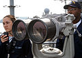 US Navy 050419-N-7526R-060 Cryptologic Technician 1st Class Jasen Williams, right, mans the Big Eyes binoculars as Operations Specialist Seaman Stephani Wood stands by, waiting to pass along any instructions as USS Blue Ridge (.jpg