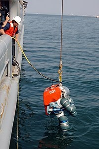 The ADS 2000 suit is lowered into the sea from the side of a ship