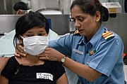 US Navy 060820-N-3153C-011 Indian Navy Cmdr. Divaya Gautam examines a patient in casualty receiving aboard the Military Sealift Command (MSC) hospital ship USNS Mercy (T-AH 19)