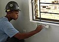 US Navy 070716-N-6999H-022 Construction Mechanic 2nd Class Josh Thomas, assigned to Amphibious Construction Battalion (ACB) 1, applies putty compound to repair a window ledge during an engineering civic action program at the Ho.jpg