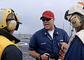 US Navy 100116-N-2000D-029 Boatswain's Mate 1st Class Howard Scales gives instructions to flight deck crew members before a crash and salvage drill aboard the amphibious dock landing ship USS Carter Hall (LSD 50).jpg