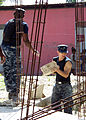 US Navy 100127-N-0924R-007 Navy Chaplain Lt. Devon Foster and Gunner's Mate 3rd Class Nicholas Bartlett remove rubble from a home in Neply during a community relations project.jpg