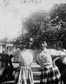 Unknown and Mary Eliza GREEN pose wearing plaid skirts in front of an old car that belonged to a relative, South Street, Raleigh, NC, 1950. Clara Meekins remembers that this car was an antique even (26480797771).jpg