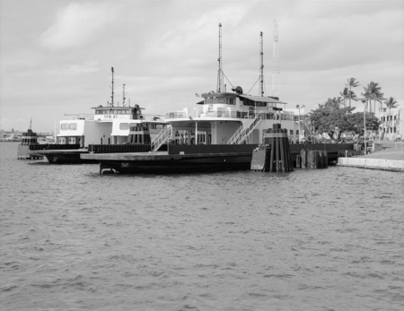 Two large ferries docked on an island on a clear day