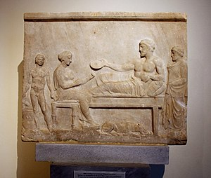 Klinai - Votive relief showing a funerary banquet. The dead man is shown as a heroized man lying on a klinai '5th century BC. On display in Room 19-20 of the National Archaeological Museum, Athens