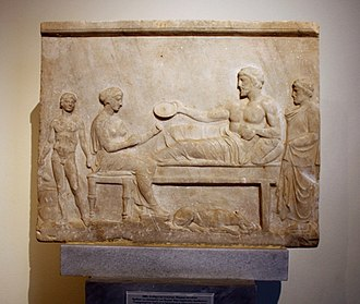 Klinai - Votive relief showing a funerary banquet. The dead man is shown as a heroized man lying on a  klinē '5th century BC. On display in Room 19-20 of the National Archaeological Museum, Athens