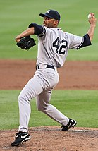 Mariano Rivera in a gray baseball uniform and navy blue cap stands on a dirt mound. His right arm is behind him, bent at the elbow and clutching a baseball. The back of his uniform shows the number 42.