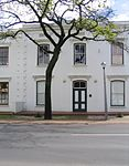 The original part of this double-storeyed town house dates from the beginning of the 19th century. The building was later adapted to the Georgian style. The property forms an essential part of the traditional architectural street scene of Dorp Street, and thus also of the historic core of Stellenbosch.