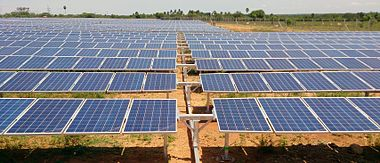 Many solar panels arranged horizontally at ground level