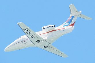 Embraer Phenom 100 - Airborne from below, clean configuration, showing its straight wing