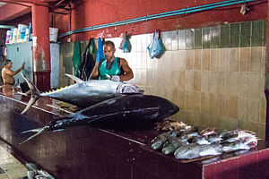 Fishmonger - A fishmonger prepares to clean and butcher a pair of large fish in Malé.