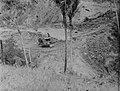 A man in a bulldozer ascending a dirt slope (AM 77376-1).jpg