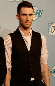 A man with a black vest and a white shirt posing on red carpet at an award show