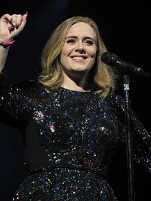 Adele holding a microphone singing
