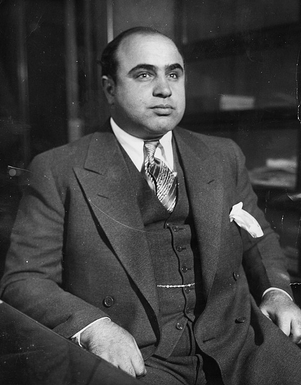 """Scarface"" Al Capone is shown here at the Chicago Detective bureau following his arrest on a vagrancy charge as Public Enemy No. 1 in this 8 x 10 black & white original wire photograph that has attached the original news bureau caption on verso, dated ""2-26-31."""