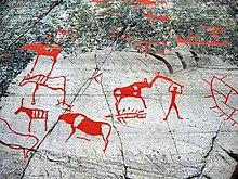 Dessins rouge vifs sur des pierres, représentants des animaux et un homme les chassant