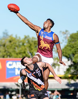 Australian rules football - A ruckman leaps above his opponent to win the hit-out during a ball-up