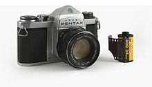 An Asahi Pentax S3 camera, facing slightly off-center, with a roll of 35mm film to one side to provide scale