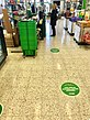 Signs on the Terrazzo floor at the checkout in Coop, Åmål to facilitate social distancing while queuing, as well as plexiglass shields to protect checkout staff from catching the disease.