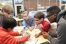 Five middle school students work together at a table using a soldering iron.