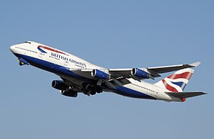 A British Airways 747-400 in white, blue an reid livery during takoff wi its landin gear retractin.