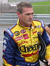 A man in his early forties wearing yellow racing overall and he is holding a HANS device