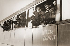 """Œuvre de secours aux enfants - Jewish youth liberated at Buchenwald lean out the windows of a train, as it pulls away from the station. The train, which has been marked with the phrase """"Hitler kaput"""" (""""Hitler is finished"""" in several European languages), will transport the children to an OSE home in Ecouis, France."""