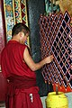 Buddhist monk making 'ghost catcher' (8083302356).jpg