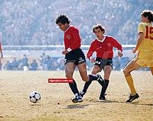 Photographie en couleurs. Un joueur en maillot rouge et short noir court vers la gauche après un ballon, observé par un autre joueur de la même équipe et un autre tout en jaune.