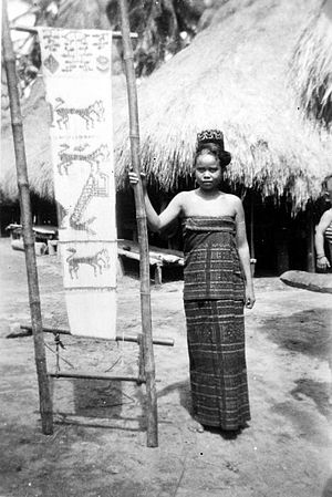 Ikat - Young woman from Kambera, Sumba, wearing an ikat garment and with the warp for a cloth tied and ready for dying. 1931