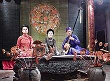 Drei Musiker treten auf einer Bühne auf.