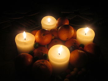 English: Candles light a plate of oranges and ...