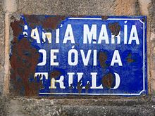 "A very rusty metal sign covered in blue enamel with white enamel lettering, the sign affixed to a stone wall. The words on the sign are ""Santa María de Óvila Trillo""."