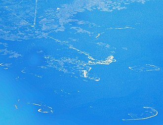 Cedar Key, Florida - Aerial view of Cedar Key and its outlying islands, illustrating the extremely small size of the city:  The fork at State Roads 24 and 347 (the only two access roads) can be seen in the upper left.