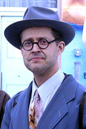Photograph of a man in a formal suit, hat, and glasses