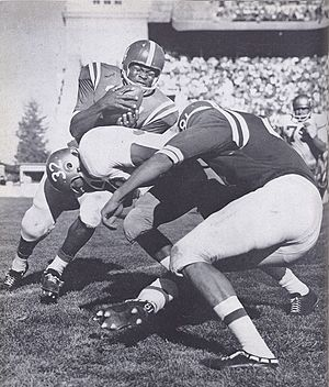 End run - Clay White attempts an end run during a 1959 game.