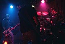 Una banda de rock australiana, Cosmic Psychos, actuando en el escenario.  El escenario oscuro está iluminado por luces de colores.  Se ven tres artistas: un bajista eléctrico, un guitarrista eléctrico y un baterista detrás de una batería.