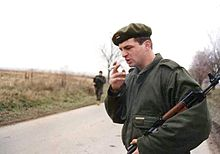 A young man wearing battledress and a beret with a Serbian flag badge stands on a road, smoking a cigarette and holding an AK-47 rifle in the crook of his arm.