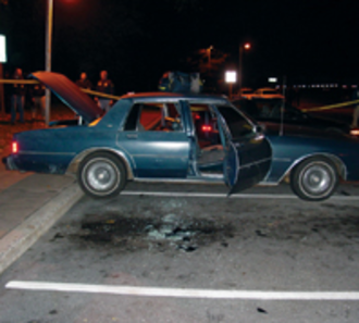 D.C. sniper attacks - The blue 1990 Chevrolet Caprice driven by Muhammad and Malvo, at the rest area where they were captured. Glass shards on the ground are a result of the shattering of the car's windows during the arrest.