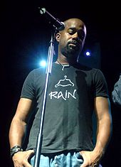 A dark-skinned man in a t-shirt and jeans standing at a microphone