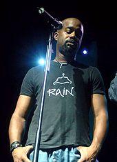 Темнокожий мужчина в футболке и джинсах стоит у микрофона