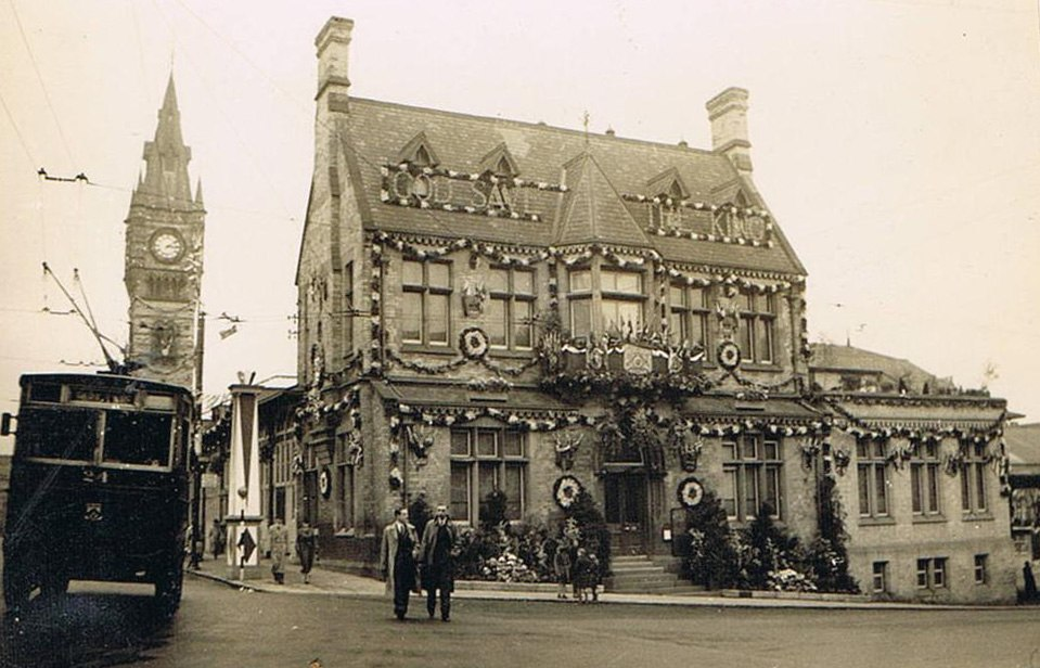 """Three-storey Victorian building festooned with garlands with the words """"God Save the King"""" mounted on the pitched roof"""
