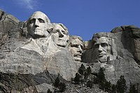 Heads of four presidents carved into the mountain with blue sky