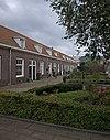 foto van Dubbele rij van vierentwintig rug-aan-rug gebouwde woningen op rechthoekige plattegrond, bestaande uit een bouwlaag onder een met pannen gedekt mansardedak