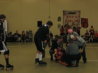 Emergency medical technician - EMTs tend to a woman with a spiral fracture at a roller derby bout.