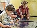 Des visiteurs évaluant les fonctionnalités d'une table tactile, musée du Louvre 2013.jpg