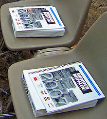 "A book titled ""Dunder Mifflin 2007 Annual Report"" on top of a ream of paper in two empty plastic chairs"