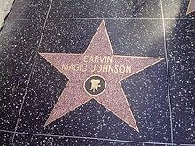 """Kvin-pinta stelo gravurita sur kahelo. En la centro de la stelo estas la vortoj """"EARVIN MAGIC JOHNSON"""". Bildo de filmilo estas gravurita rekte sub tiuj vortoj, kvankam daŭre en la stelo."""
