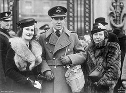 Photograph of a man with two women. The man is in the centre, wearing military uniform, a cap and a large coat, with a bag over his shoulder. He is holding the hand over the younger woman on his right. Both women are dressed formally, with hats and fur coats.